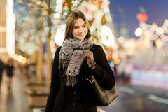 Photo of woman outside in city on blurred background with garland royalty free stock photos