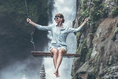 Photo of Woman Riding Swing in Front of Waterfalls royalty free stock image