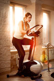Photo of woman riding trainer bike at fitness club Stock Photo