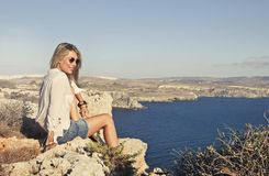 Photo of a Woman Sitting on the Cliff Royalty Free Stock Photo