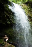 Photo of Woman Sitting on Rock Facing the Waterfalls royalty free stock photos