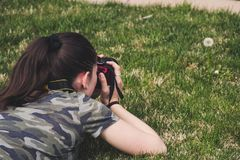 Photo of Woman Taking Photo of Flower on Grass royalty free stock image