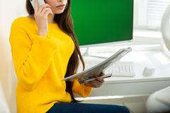 Photo of woman, talking on phone and reading documents in office. Green screen in the background stock photography