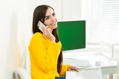 Photo of woman, talking on phone and reading documents in office. Green screen in the background royalty free stock image