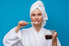 Photo of woman with toothbrush and mug of coffee. On empty blue background stock images