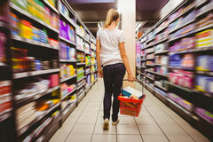 Photo of a woman walking with his trolley on aisle on selective focus Stock Photo