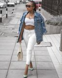 Photo of Woman Wearing White Crop Top and Denim Jacket Walking in Pavement Holding Bag stock photos