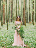 The photo of the woman in the wedding pink dress looking at the big bouquet of red, white flowers and green grass at the Royalty Free Stock Images