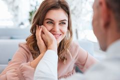 Photo of woman in love looking on her man and taking pleasure wh. Photo of women in love looking on her men and taking pleasure when holding male hand at her Stock Photo