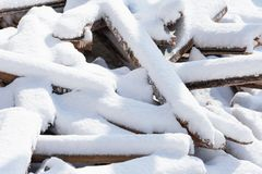 Wooden bars and planks, chaotically dumped in a pile, covered with white snow. Photo of wooden bars and planks, chaotically dumped in a pile, covered with white royalty free stock photos