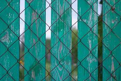 Photo of wooden fence in summer garden with fencing mesh royalty free stock photography