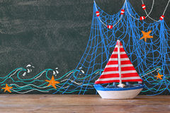 Photo of wooden sailing boat in front of chalkboard with nautical illustrations.