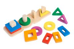 Photo of a wooden toy. Children`s sorter with small wooden details in the form of geometric shapes rectangle, square, circle, triangle, in different colors  on Royalty Free Stock Photography
