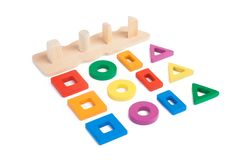 Photo of a wooden toy. Children`s sorter with small wooden details in the form of geometric shapes rectangle, square, circle, triangle, in different colors and royalty free stock photos