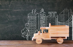 Photo of wooden toy truck in front of chalkboard with city illustration. Royalty Free Stock Image