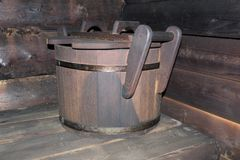 Wooden old tub for water in the bath. Photo wooden tub with handles and lid.water tank.steam room made of wooden planks.the bucket is on the shelf stock photo
