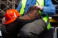 Worker sitting with leather boot stock photography