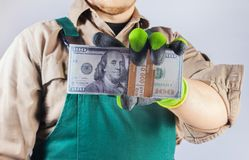 Photo of a worker in green overall outfit holding money. Photo of a worker in green overall outfit with protective gloves holding pack of dollar banknotes, torso royalty free stock photography