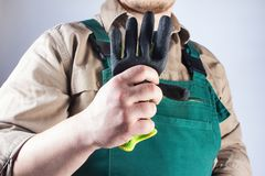 Worker in green overall outfit holding glove. Photo of a worker in green overall outfit holding protective rubber glove on grey background torso view stock photo