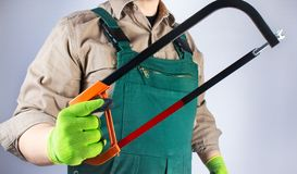 Worker in green overall outfit with hacksaw stock photo