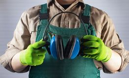 Worker in green overall outfit with headphones royalty free stock photography
