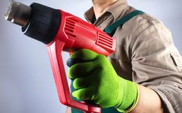 Worker in green overall outfit with heat gun tool royalty free stock image