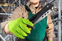 Worker in green overall outfit with riveter tool stock images