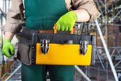 Worker in green overall outfit with toolbox royalty free stock photos