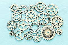 Photo of working system of cogwheels,concept of teamwork, wooden textured background. Working system of cogwheels, teamwork, flat lay, pastel yellow background royalty free stock photos