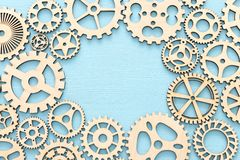 Photo of working system of cogwheels,concept of teamwork, wooden textured background. Working system of cogwheels, teamwork, flat lay, pastel yellow background stock photos