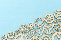 Photo of working system of cogwheels,concept of teamwork, wooden textured background. Working system of cogwheels, teamwork, flat lay, pastel yellow background royalty free stock photo