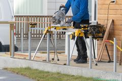 Photo of workman using chop saw to making his job. Cropped photo of unrecognizable adult workman working with a chop saw standing outside of wooden house stock images