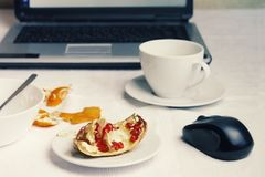 A photo of workplace after breakfast. A cup of coffee with laptop on white tablecloth, empty bowl with porridge leftovers, half of Royalty Free Stock Photo