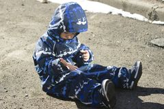 A 2-year-old boy sitting and looking on his hands. Photo of a a 2-year-old boy, wearing coveralls, sitting on the ground and looking on his hands with interest stock photography
