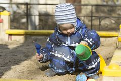 A 2-year- old boy playing in a sandbox. Photo of a 2-year-old boy, wearing dark white-blue-black coverall, playing in a sandbox in early spring. Concept of happy Stock Photos