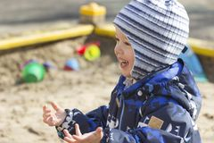 A smiling 2-year- old boy playing in a sandbox. Photo of a 2-year-old boy, wearing dark white-blue-black coverall, playing in a sandbox, happily smiling in early Royalty Free Stock Photo