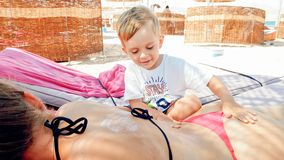 Photo of cute 3 years old little boy making massage to young mother relaxing on the sun bed at sea beach royalty free stock images