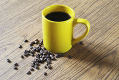 Photo of yellow cup of coffee and coffee beans on wood texture background stock image