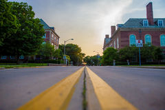 Photo of Yellow Paint Straight Line on Road Between Brown Building Stock Photography