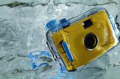 Photo of yellow waterproof camera in water with splash. Royalty Free Stock Photos