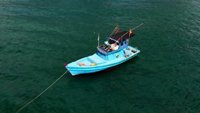 Small fishing boat standing on a long line stock photography