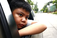 Young Asian boy looking out a car window royalty free stock photos