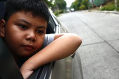 Young Asian boy looking out a car window royalty free stock photo