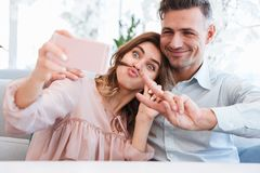 Photo of young and beautiful couple making selfie and fooling ar Royalty Free Stock Image