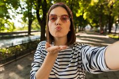Beautiful excited cute woman outdoors take a selfie by camera blowing kisses. royalty free stock photography