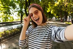 Beautiful excited cute woman outdoors take a selfie by camera winking. royalty free stock photo