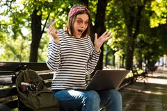 Excited happy woman outdoors sitting using laptop computer. stock photos
