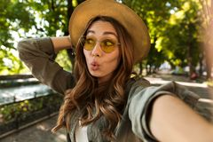 Beautiful excited shocked woman outdoors take a selfie by camera. royalty free stock images