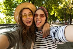 Beautiful excited women friends outdoors take a selfie by camera. stock image