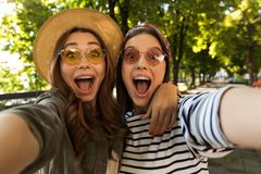 Beautiful excited women friends outdoors take a selfie by camera. royalty free stock photos